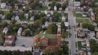 AX0003_006 - 5K stock footage aerial video of flying over residential neighborhood, tilt to church, at sunset, Calumet City, Illinois