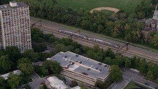 AX0003_021 - 5K stock footage aerial video of a commuter train passing through Kenwood, Illinois, twilight