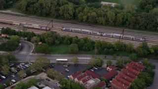 AX0003_022 - 5K stock footage aerial video of tracking a commuter train traveling through Kenwood at twilight, reveal apartments and strip mall, Chicago, Illinois