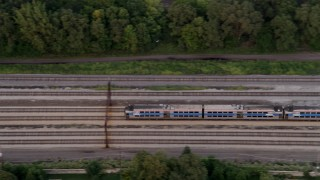 AX0003_023 - 5K stock footage aerial video of tracking a commuter train traveling through Kenwood at twilight, Chicago, Illinois