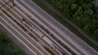AX0003_024 - 5K stock footage aerial video of a bird's eye view of a commuter train traveling through Kenwood at twilight, Chicago, Illinois