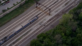 AX0003_025 - 5K stock footage aerial video of a bird's eye of a commuter train speeding through Kenwood at twilight, Chicago, Illinois