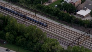 AX0003_026 - 5K stock footage aerial video of a commuter train passing through Kenwood, Chicago, Illinois, twilight