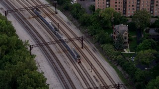 AX0003_027 - 5K stock footage aerial video track commuter train traveling through Kenwood at twilight, Chicago, Illinois