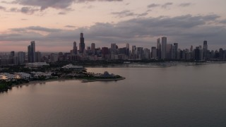 AX0003_029 - 5K stock footage aerial video of Downtown Chicago skyline and the Adler Planetarium seen from Lake Michigan at sunset, Illinois