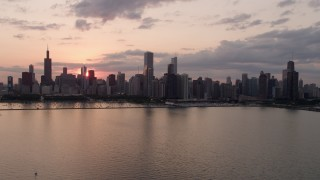 AX0003_032 - 5K stock footage aerial video of the Downtown Chicago skyline seen from Lake Michigan, on a cloudy day at sunset, Illinois