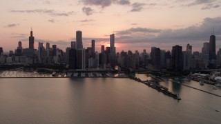 AX0003_033 - 5K stock footage aerial video of the Downtown Chicago skyline, reveal Navy Pier, cloudy sunset, Illinois
