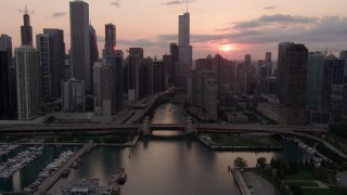 AX0003_034 - 5K stock footage aerial video tilt from the lake to reveal Downtown Chicago at sunset with clouds, Illinois
