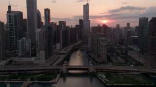 AX0003_035 - 5K stock footage aerial video approach and fly over the bridge at mouth of Chicago River at sunset, Downtown Chicago, Illinois