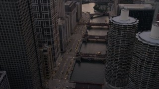 AX0003_039 - 5K stock footage aerial video of following the river through downtown past Marina City at sunset, Downtown Chicago, Illinois