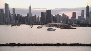 AX0003_065 - 5K stock footage aerial video of the Downtown Chicago skyline and Navy Pier, revealing lighthouse with clouds at sunset, Illinois