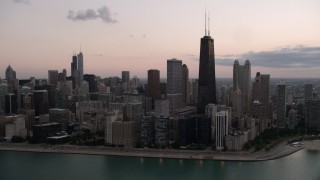 AX0003_070 - Aerial stock footage of John Hancock Center and lakefront skyscrapers, seen from Lake Michigan, with clouds at twilight, Illinois