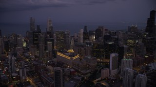 AX0003_114 - 5K stock footage aerial video of a view across Downtown Chicago at sunset, with Lake Michigan in the background at twilight, Illinois