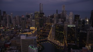 AX0003_116 - 5K stock footage aerial video of approaching bridges over the Chicago River and skyscrapers, Downtown Chicago, Illinois, twilight