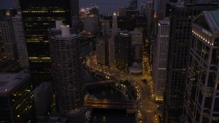 AX0003_118 - 5K stock footage aerial video fly over bridges and follow the Chicago River through downtown at twilight, Downtown Chicago, Illinois