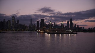 AX0003_128 - 5K stock footage aerial video of flying by Navy Pier with the Downtown Chicago skyline in the background at twilight, Illinois