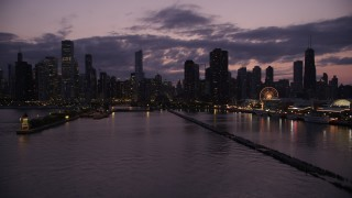 AX0003_129 - 5K stock footage aerial video of flying over Lake Michigan to approach Downtown Chicago skyline at twilight, Illinois