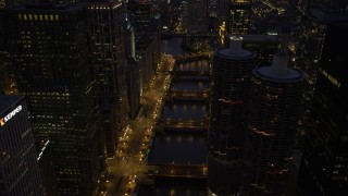 AX0003_135 - 5K stock footage aerial video follow the Chicago River over bridges and tilt up, Downtown Chicago, Illinois, twilight