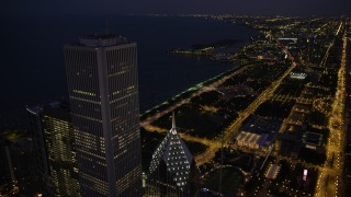 AX0003_145 - 5K stock footage aerial video of flying by Two Prudential Plaza and Aon Center to approach Grant Park at night, Downtown Chicago, Illinois