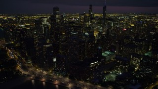 AX0003_161 - 5K stock footage aerial video of flying by Downtown Chicago cityscape, at night with clouds, Illinois
