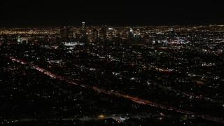 AX0004_018 - Aerial stock footage of Tilt Up and Reveal Downtown Los Angeles Skyscrapers at Night