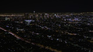 AX0004_018E - 5K stock footage aerial video tilt and reveal Downtown Los Angeles skyscrapers at night, California