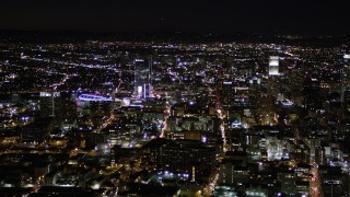 AX0004_025 - Aerial stock footage of Orbit Skyscrapers near Staples Center at Night in Downtown Los Angeles