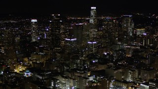 AX0004_027 - Aerial stock footage of Tilt Up to Reveal Downtown Los Angeles Skyscrapers at Night