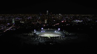 AX0004_036 - 5K stock footage aerial video tilt to reveal Dodger Stadium and Downtown Los Angeles skyline at night, California