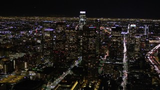AX0004_039 - Aerial stock footage of Approach Downtown Los Angeles Skyscrapers at Night