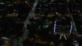 AX0004_055 - 5K stock footage aerial video pan across streets and skyscrapers at night in Downtown Los Angeles, California
