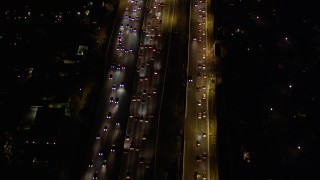 AX0004_094 - Aerial stock footage of Flying Over Rush Hour Traffic at Night in Brentwood