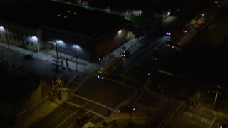 AX0004_104 - 5K stock footage aerial video of reverse view of a city street at night in Pacoima, California