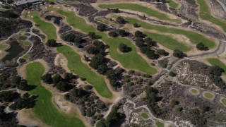 AX0005_013 - 5K stock footage aerial video of orbiting green golf course lawns in Canyon Country, California