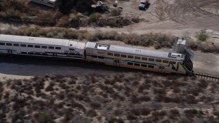 AX0005_026 - 5K stock footage aerial video of tracking a Metrolink commuter train in the Santa Clarita Countryside in California