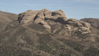 AX0005_032 - 5K stock footage aerial video reveal and approach Mojave Desert rock formations in California