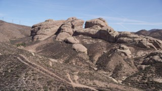 AX0005_033 - 5K stock footage aerial video approach large Mojave Desert rock formations in California