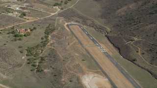 AX0005_048 - 5K stock footage aerial video orbit runways at a desert airfield in Agua Dulce, California