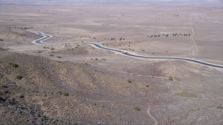 AX0005_058 - 5K stock footage aerial video approach desert aqueduct from arid mountains in the Mojave Desert