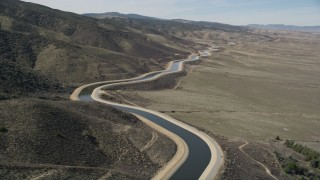 AX0005_063 - 5K stock footage aerial video fly low over the desert to reveal California Aqueduct in Mojave Desert