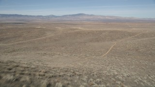 AX0005_069E - 5K stock footage aerial video fly low over open desert and arid hills to reveal solar array in Antelope Valley, California