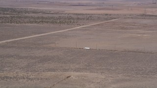 AX0005_073 - 5K stock footage aerial video of tracking a big rig on a desert road in Antelope Valley, California