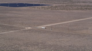 AX0005_074 - 5K stock footage aerial video of tracking big rig and SUV on desert road through Antelope Valley, California