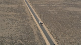 AX0005_075 - 5K stock footage aerial video orbit a big rig and SUV on a desert road in Antelope Valley
