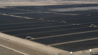 AX0005_080 - 5K stock footage aerial video orbit a large array of solar panels in the desert in Antelope Valley, California