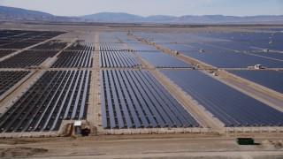 AX0005_083 - 5K stock footage aerial video of passing rows of solar panels in a massive desert array in the Mojave Desert, California