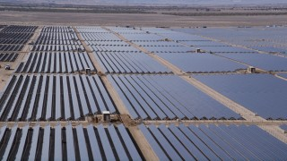 AX0005_084 - 5K stock footage aerial video orbit rows of panels at a massive solar array in the Mojave Desert, California