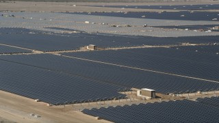 AX0005_084E - 5K stock footage aerial video orbit rows of panels at a massive solar array in the Mojave Desert, California