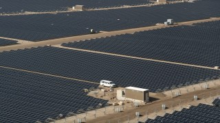 AX0005_086 - 5K stock footage aerial video orbit rows of solar panels at an array in the Mojave Desert, California