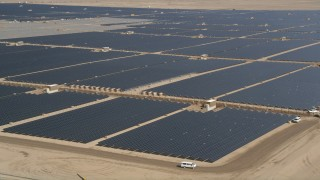 AX0005_088E - 5K stock footage aerial video of circling solar panels at a solar energy farm in the Mojave Desert, California